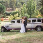 Bride and groom in front of our vintage limousines