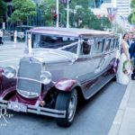 Bride and groom standing next to wedding limousine