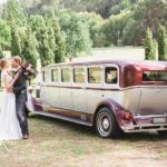 Bride and groom standing next to limousine