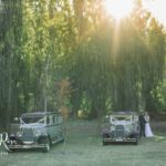 Bride and groom next to our vintage limousines