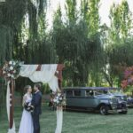 Bride and groom in front of vintage limousines